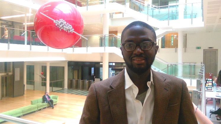 Atta Addo standing in a large foyer of a building | LSE researcher profiles