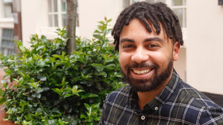 A smiling man in an outdoor setting | Celestin Okoroji | researcher at LSE