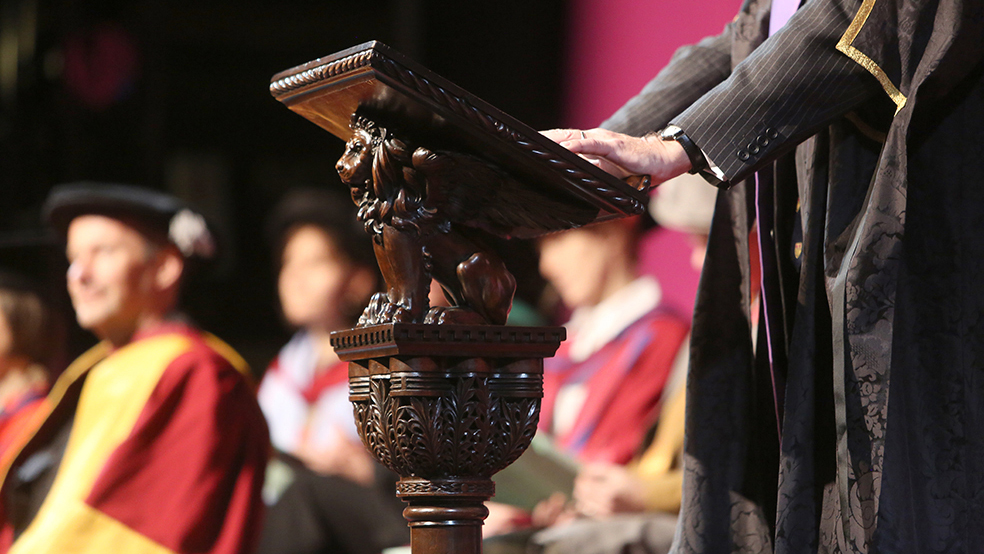 A person in academic robes stands at an old carved lectern during graduation